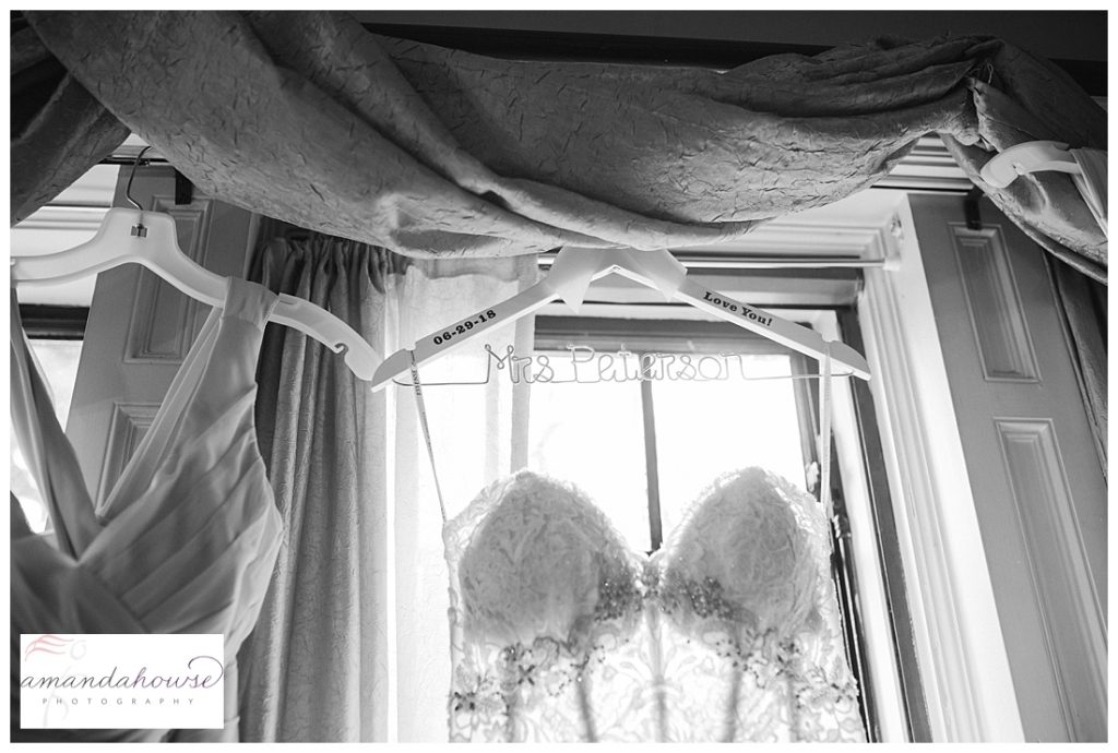 Sheer lace wedding gown hanging in the window photographed by Tacoma Wedding Photographer Amanda Howse